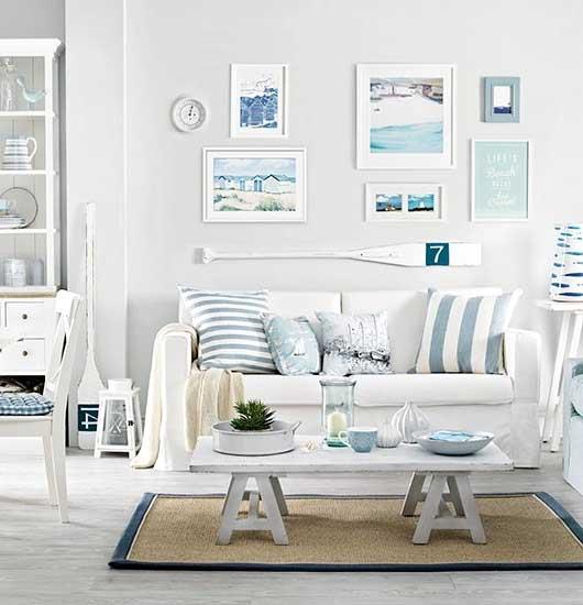 Jasna biała aranżacja pokoju dziennego z użyciem poduszek dekoracyjnych